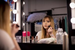 A young person applies make-up while looking into a mirror