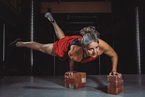 Photo of a woman using her arms to balance on raised bricks